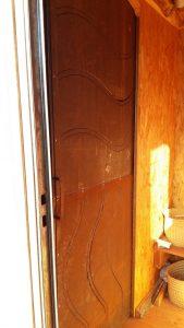 Porte tôlée vague découpé au plasma à galandage vue depuis les toilettes sèches MetalRine