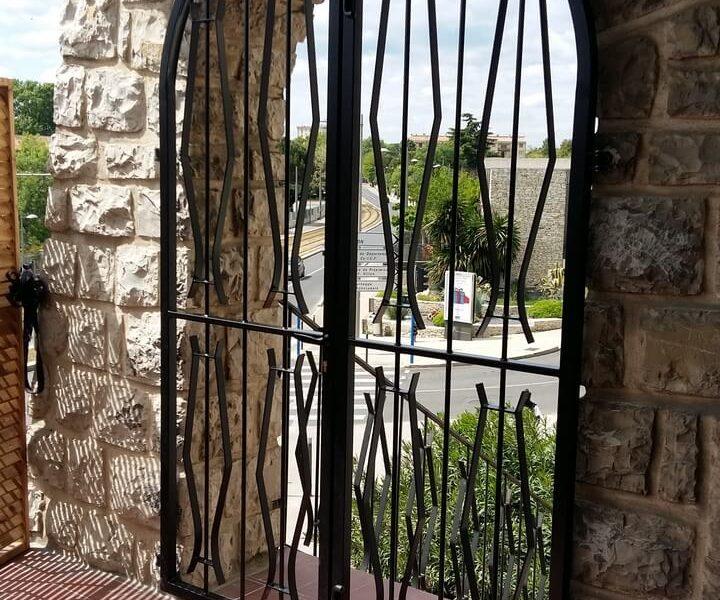 Porte double grille en arche vue terrasse Métal'Rine