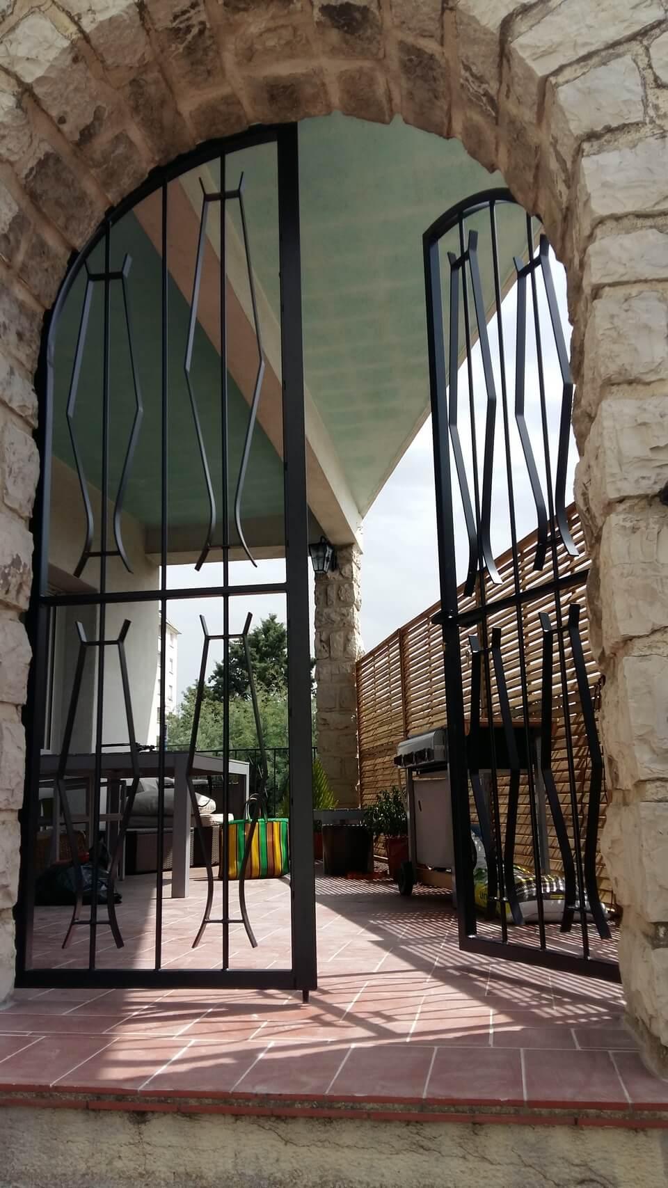 Porte double grille en arche vue des escaliers Métal'Rine